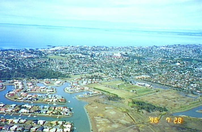 Colour photo showing canal development in foreground with Leagues Club and park on the right. Redcliffe and bay in background.