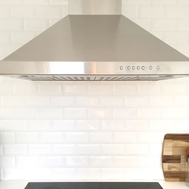 Beautiful oversized exhaust fan, ceramic cooktop, white counters against white beveled subway tile. Beautiful Scandinavian design in a little Canadian home. www.ourscandihouse.ca