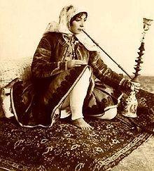 Persian woman, in Qajar era dress seen here smoking the traditional Qalyan.