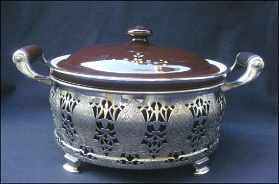 Royal Rochester covered casserole baking and serving piece with silvertone metal holder. By Rochester Stamping Company of Rochester, NY. It is marked on the bottom Royal Rochester Fire Proof China for Baking and Guernsey Cooking Ware in a circle around a large C with AP in the