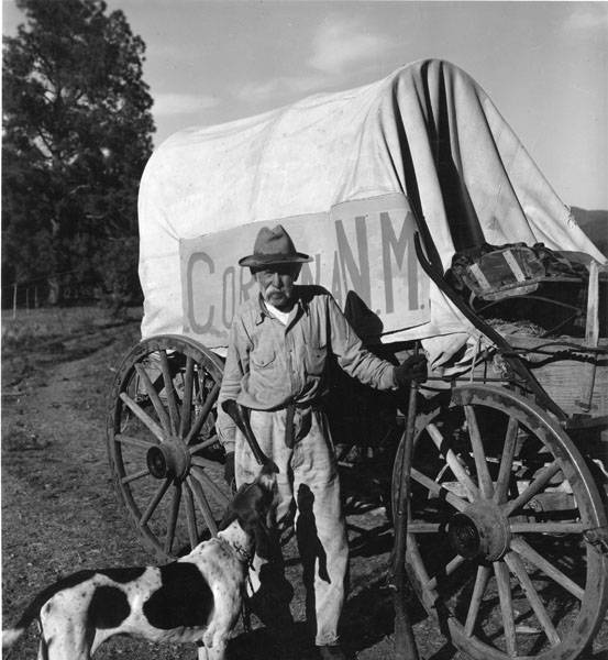 An old timer from Corona, New Mexico and his dog stand beside their covered wagon at the 1940 Frontier Days celebration in Ruidoso, New Mexico. Palace of the Governors Photo Archives HP.2007.20.650.