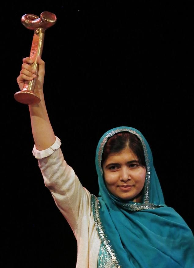 Malala raises the RAW (Reach All Women) in War Anna Politkovskaya Award after receiving it at the Southbank Centre in London on Friday.