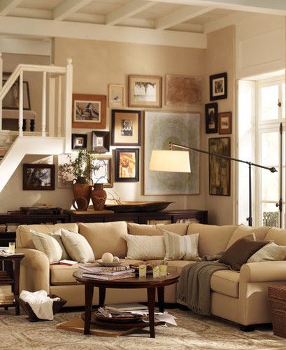 picture collage wall using different wood frames in various sizes for a neutral living room palette