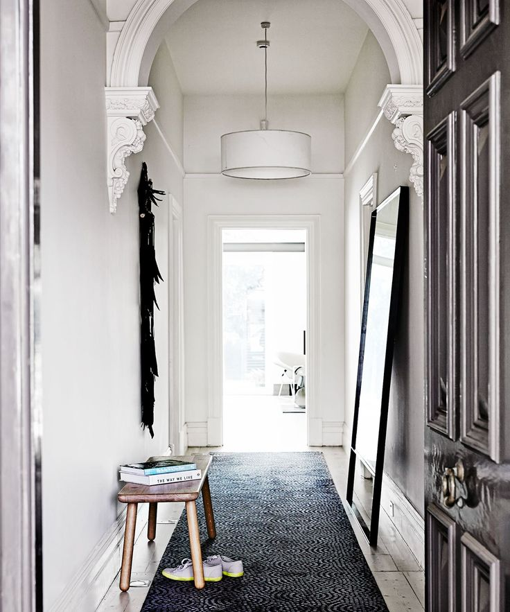 Entryway - heritage/period home: white drum shade pendant light, corbels, decorative arch, wooden bench/stool, dark charcoal grey/black hall runner carpet, modern black freestanding mirror, tall skirting boards, pale timber floorboards