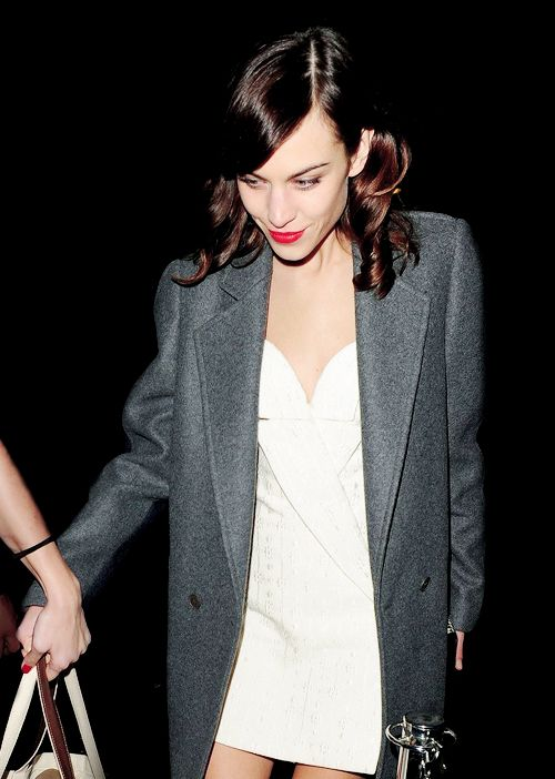 Alexa Chung in a stylish cream dress, oversized grey blazer, side hair curled with bright red lip.