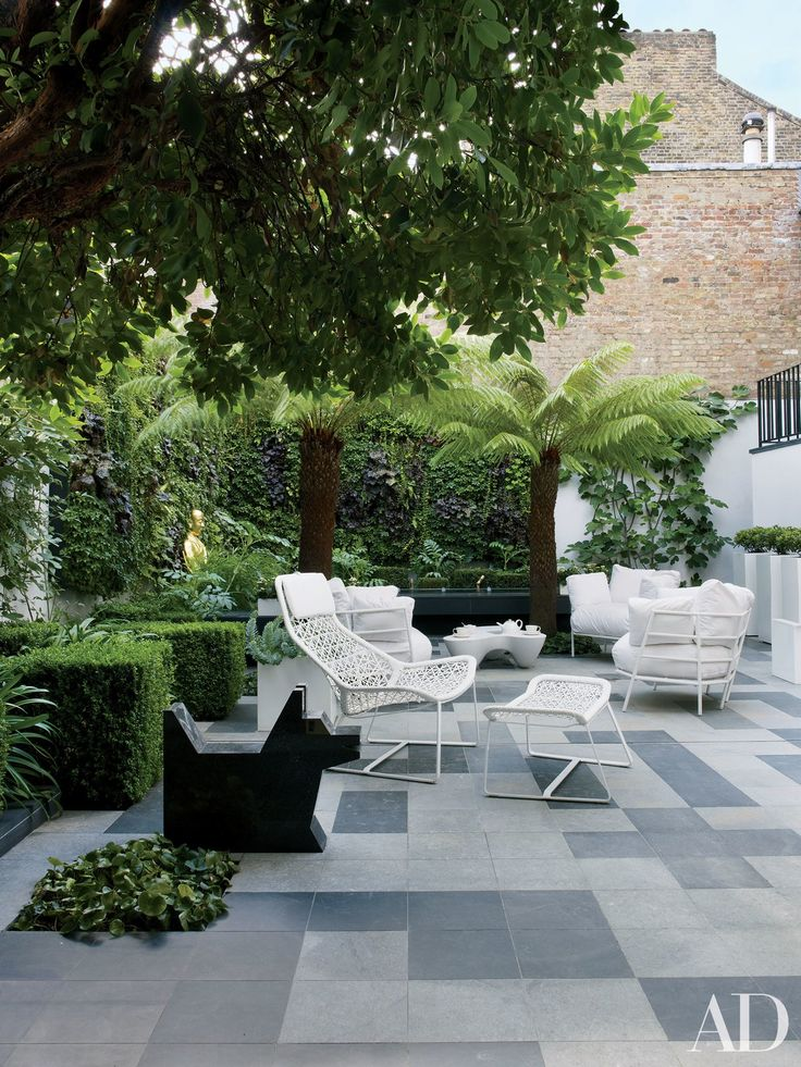 On the slate-paved terrace of a Rafael de Cárdenas–designed residence in London, a Ben Jones dog sculpture is displayed beside a lush sitting area.