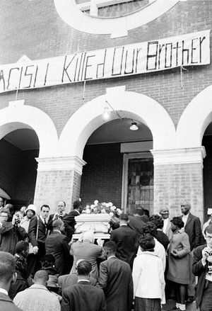 """Jimmie Lee Jackson's casket is carried into a church for funeral services on March 3, 1965, under a banner that reads """"Racism Killed Our Brother."""" The death of 26-year-old Jimmie Lee Jackson galvanized civil rights leaders across the country. Just a few days after Jackson's funeral, civil rights activists marched from Selma to Montgomery, and the police brutality during that march, known as Bloody Sunday, ultimately led to the 1965 Voting Rights Act."""