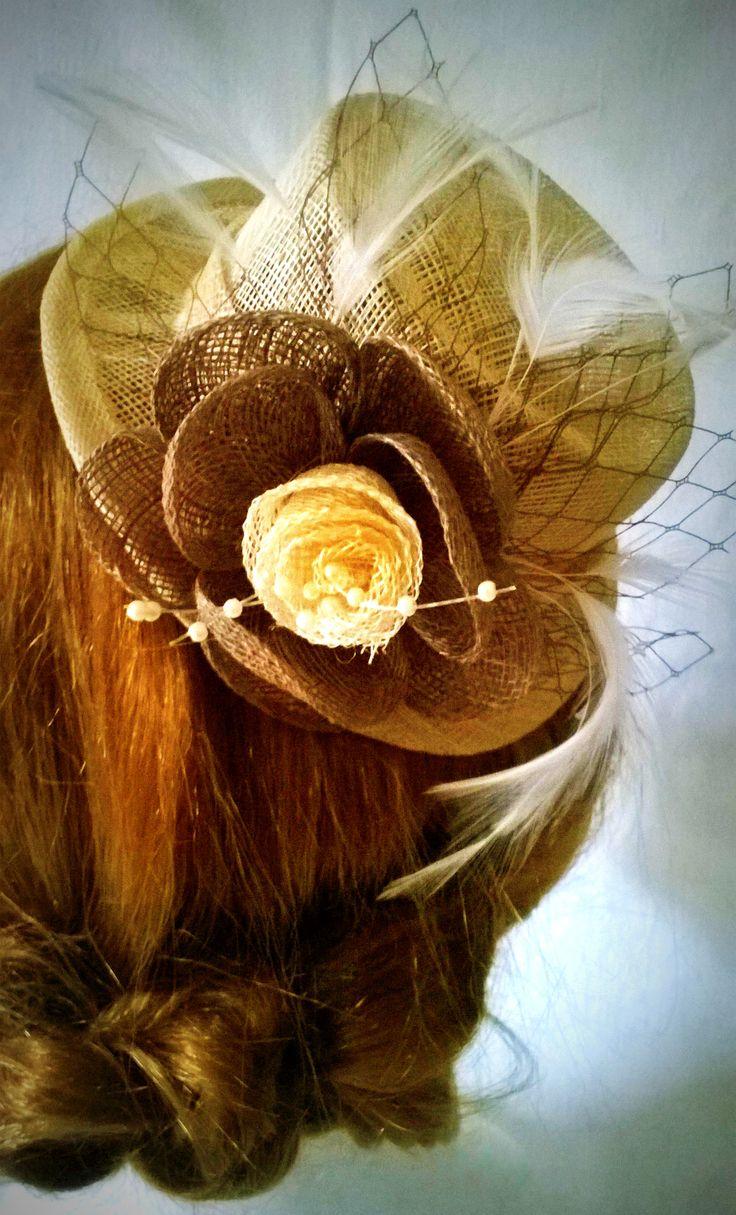 Accessorio per capelli realizzato a mano in sinamay con applicazione di fiore e piumette, adatto a tutte le occasioni.