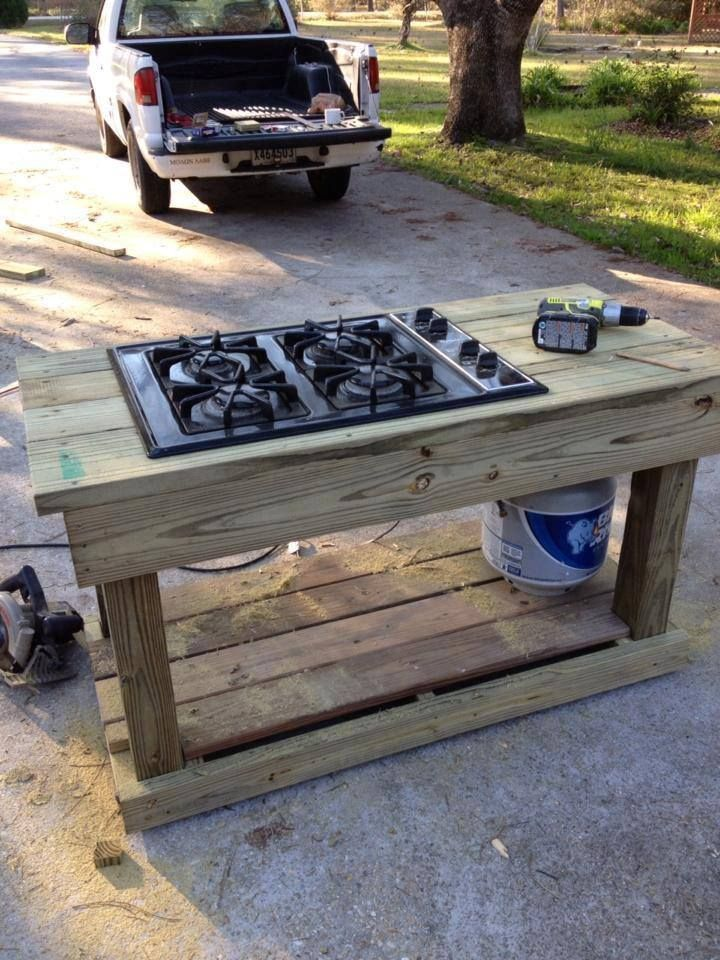 Find a gas range on craigslist or yard sale and a free table..you have an outdoor stove. also leave space for a bin and a shelf to put a water jug on and it is a full kitchen!