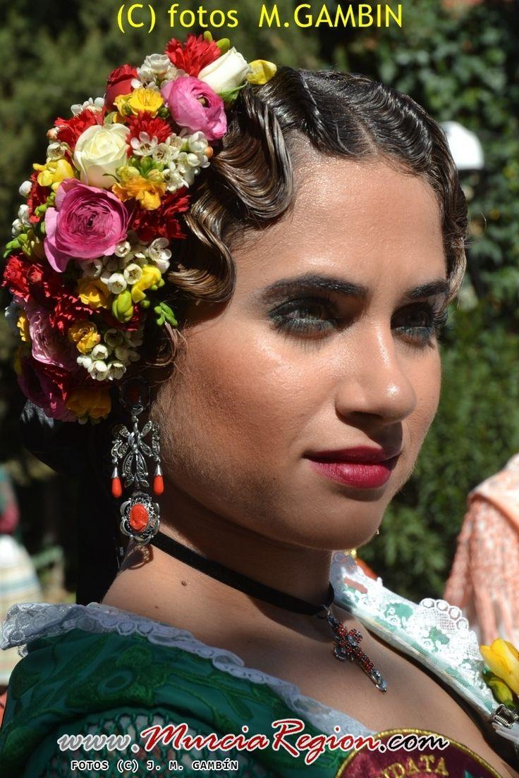 Característico tocado de flores y   y complementos como los pendientes tipo arracadas que pueden ser en oro o plata y la cruz con la cinta de terciopelo negro.