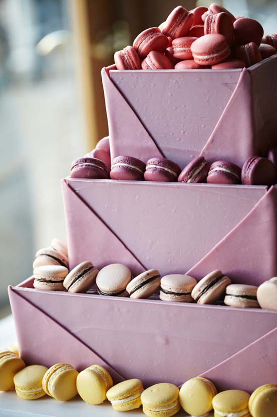 Three tiered cake boxed in pink chocolate, surrounded by macaroon edging. Yum!