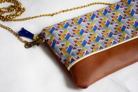 Ce petit sac Ethnique est en simili cuir marron et tissu coloré. Le verso de la pochette est composé du simili cuir marron.  La pochette est doublée d'un molleton et d'un cot - 19243173