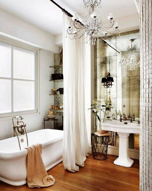 floor to ceiling privacy curtain, aged mirror wall, pedestal sink, bling chandelier. love this bath.