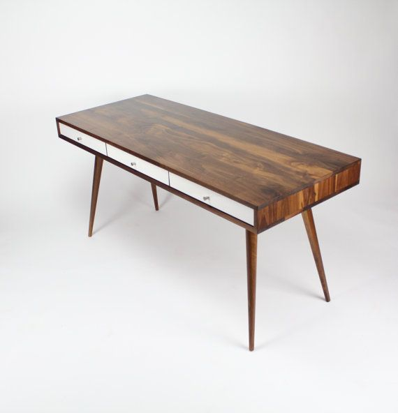 This modern classic Mid Century style desk features gloss white or walnut drawers, and an 8 cable management cubby in the back. Keep your home office space neat and tidy with this solid walnut desk. The three hardwood drawers provide ample storage space and ride on soft-close glides to give it that high end touch. The desks sits on solid walnut or oak tapered legs that bolt in to a heavy wood cleats for sturdiness and longevity. Current lead time is 6-12 weeks. Production may vary. Please…