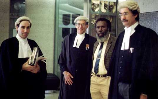 """Eddie Mabo & legal council, 1991. """"Mabo: The Native Title Revolution"""" (mabonativetitle.com). known for his role in campaigning for Indigenous land rights and for his role in a landmark decision of the High Court of Australia which overturned the legal doctrine of terra nullius (""""land belonging to nothing, no one"""") which characterised Australian law with regards to land and title."""
