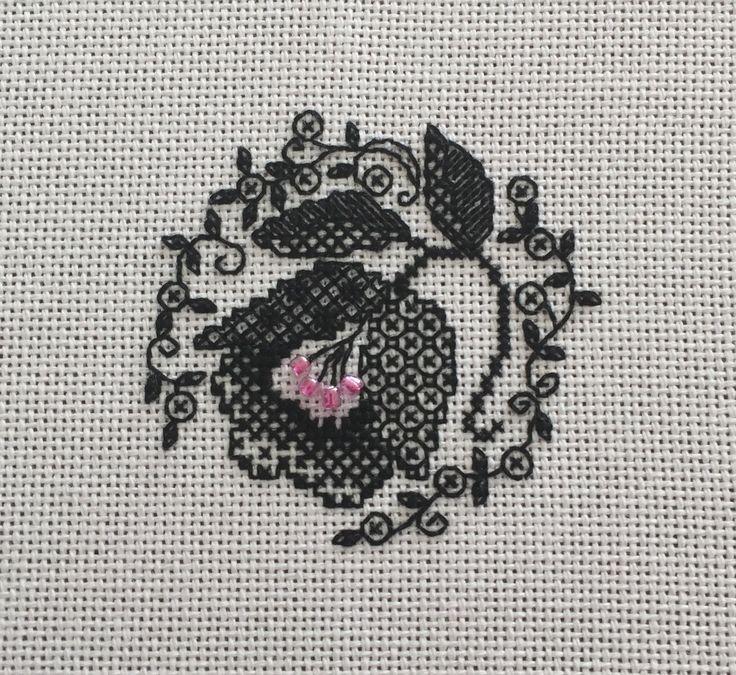 Blackwork flower on pink Lugana.