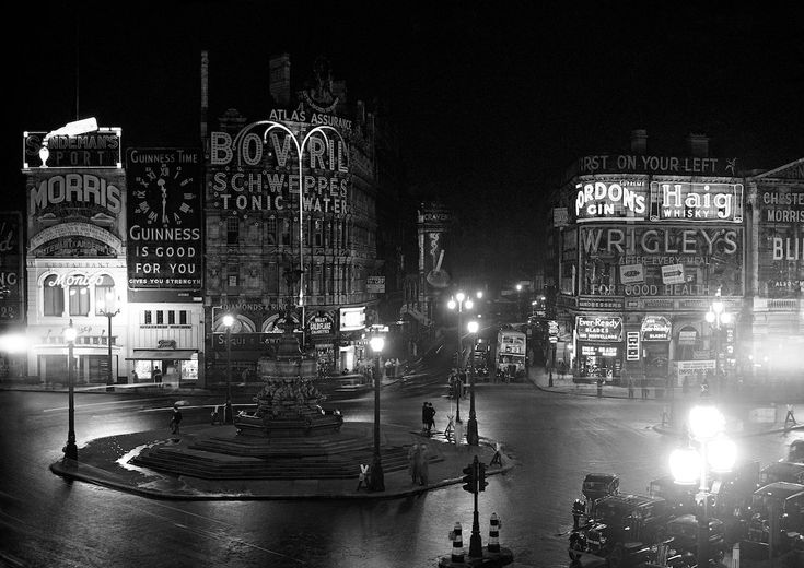 Aug. 10, 1939 This is what Piccadilly Circus in central London looked like on the night before the Blackout. Note the two bollards either side of the traffic light at the bottom of picture - they have been painted with white stripes to be more visible when the Blackout begins, as have the wooden strut supports at the base of the central street lights. Small, dimmer, lamps are hung from these struts.