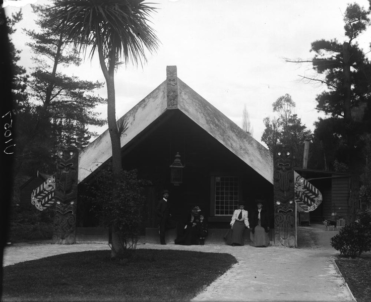 Four adults and a child outside a whare, 1908
