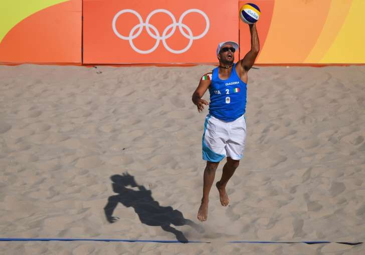 Adrian Carambula Raurich of Italy serves during the Men's Beach Volleyball preliminary round Pool A match against Clemens Doppler and Alexander Horst of Austria on Day 1 of the Rio 2016 Olympic Games at the Beach Volleyball Arena on August 6, 2016 in Rio de Janeiro, Brazil.