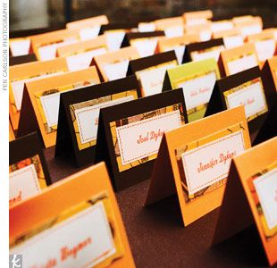 autumn escort cards _ orange thread used to attach cream-colored name cards onto poppy-patterned fabric and a folded cardstock base.