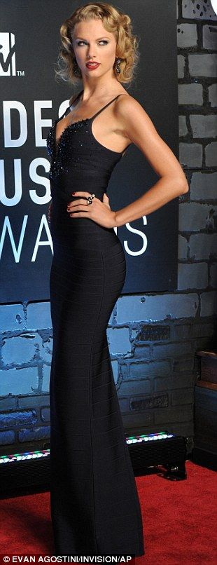 Channelling old glamour: Tyalor Swift looked very vintage Hollywood in her plunging navy blue gown and curled blonde hair