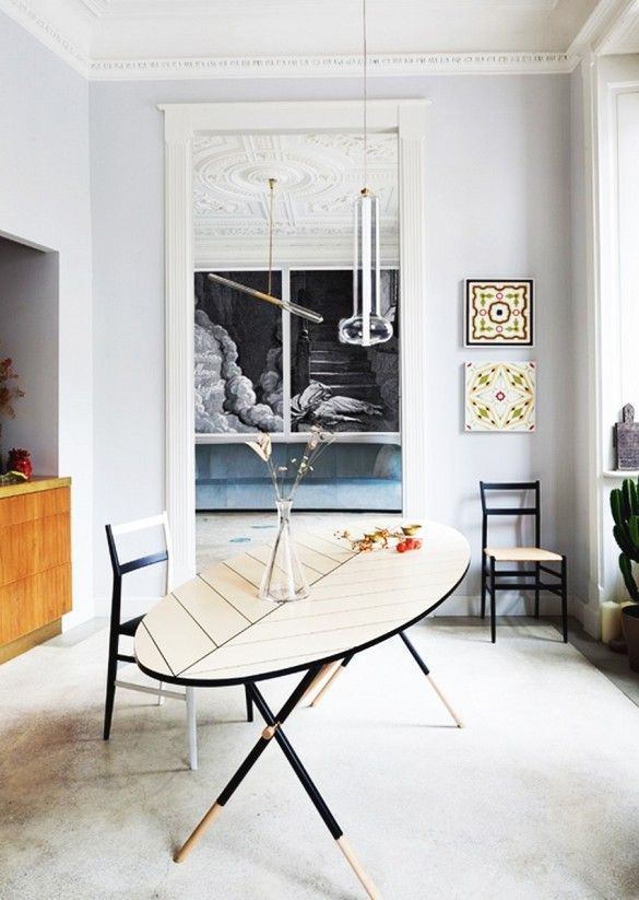 A oval shaped table, white rug, off-white walls, tile paintings, clear lamp, and black wooden chairs