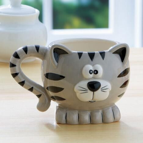 """Give your favorite cat lover a gift that will be appreciated every day. Ceramic mug is 4"""" tall, with a cat's-tail handle! Details: Dishwasher/microwave safe. Ho"""