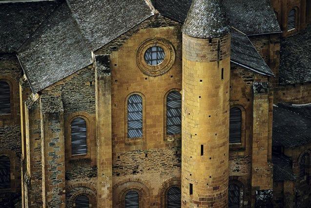 Eglise Saint-Foy de Conques, début du XIIe siècle : vue des murs gouttereaux du transept saillant dont les fenêtres sont ornés de vitraux réalisés par Pierre Soulage.
