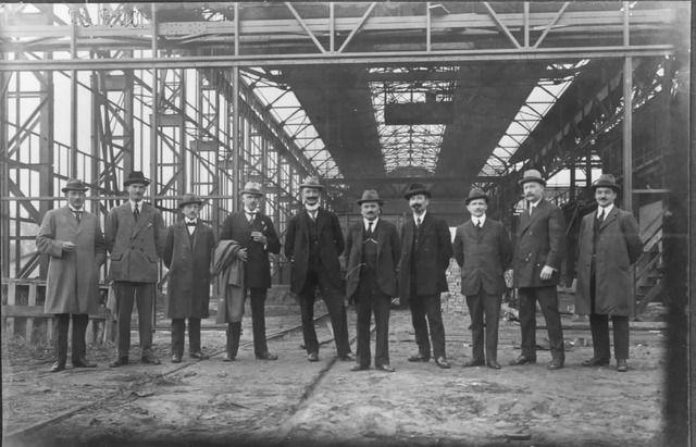 Groepsportret in de giethal/vormerij van de fabriek van de N.V. Nederlandse Staalfabrieken DEMKA voorheen J.M. de Muinck Keizer (Havenweg 7) te Zuilen, tijdens de bouw; op de voorgrond een rij heren, poserend voor de fotograaf; vijfde van rechts de heer J.M. de Muinck Keizer, direkteur van de fabriek. N.B. De Havenweg is per 1 januari 1954 bij de gemeente Utrecht gevoegd. 1915-1925