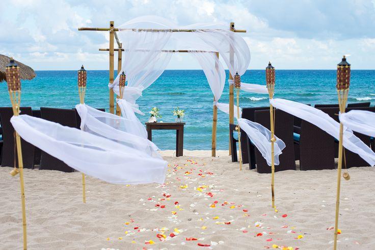 Montaje de boda civil en la playa con gazebo y antorchas de bambú y telas…