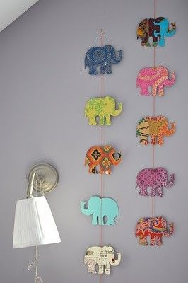 Elephant wall art - Cut out elephant shapes with cardboard and paint patterns on it. attach with string and it makes a beautiful decoration!