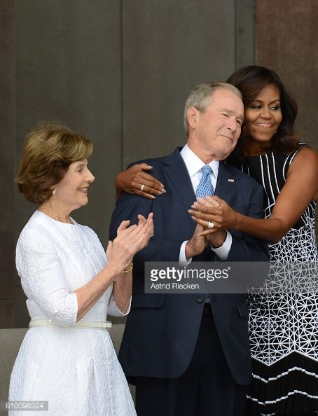 First lady Michelle Obama embraces former president George Bush accompanied by his wife former first lady Laura Bush while participating in the...