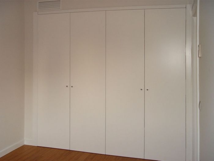 Diseño y fabricación de armario a medida lacado en blanco brillo con puertas abatibles