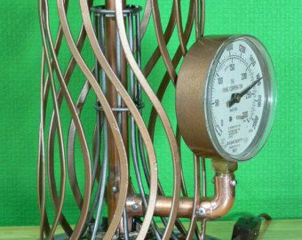 Steampunkd - Starting with a solid Brass Kerosene Fuel Tank from a 100 year old Perfection heater. Polished the brass and started building this cool lamp. The fuel tank has a fuel gauge, a fill cover and a knob for winding the wick. Includes one large softball size 40 watt Edison bulb. One gauge mounted via copper pipe soldered and riveted, one coil made from 1/8 copper tubing. The tank has 12 brushed gold finish gears applied to it, they were cut from a metallic material and applied on the…