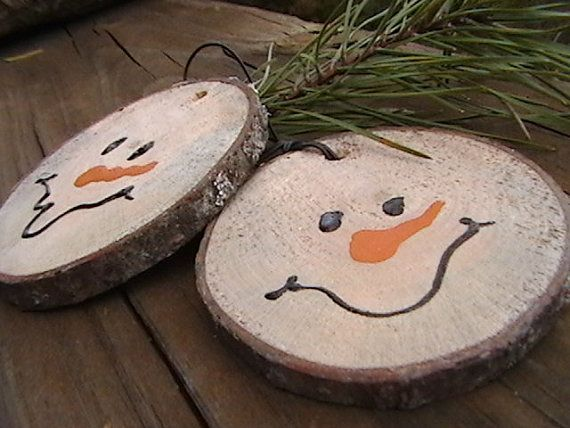Snowmen made out of branches. Cut the branch and drill a hole at the top to attach a string. Make sure name and year are on the back!