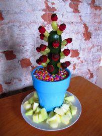Traktatie: fruitige cactus  Nodig:   •  2 courgettes     •  aardbeien     •  reep chocolade     •  coctailprikkers     •  bloempot     •  tuinaarde         Werkbeschrijving   •doe de tuinaarde in de bloempot, steek de courgettes erin   •smelt de chocolade au bain marie en dip hierin de aardbeien   •steek de aardbeien in de courgette met de coctailprikkers en klaar!   Bron: www.party-kids.nl