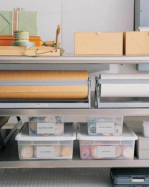 An extra-long stainless steel kitchen table holds crafts supplies -- many organized in clear plastic bins with press-on label sleeves. A paper cutter (on the tabletop) is a useful tool. This table is also used for unwrapping packages.