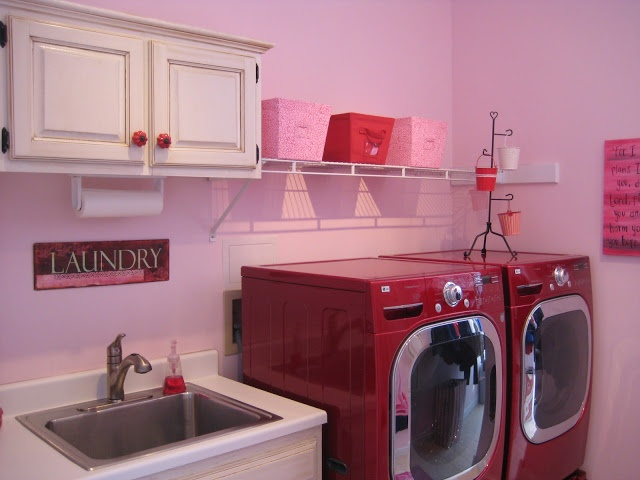 Pink laundry room with red washer/dryer units :)