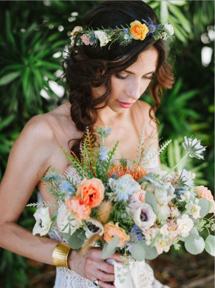 the bride in her flower crown and holding her bouquet wrapped in cream muslin and made of orange protea, light blue nigella, blue thistle, white anemone, peach stock, white scabiosa, Juliet garden rose, silver dollar eucalyptus, and peach ranunculus and