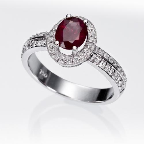Anillo orla rubí y diamantes. Anillo en forma de orla con un rubí central talla oval en garras y diamantes talla brillante (0.35 quilates), engastados en montura de oro blanco de 18 kilates