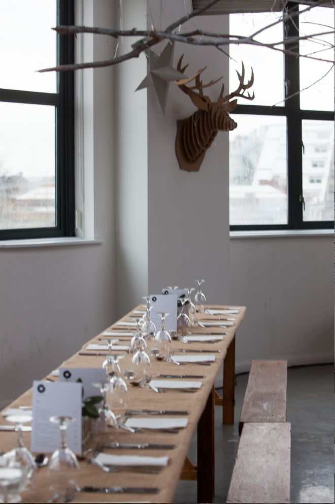 The space is set up in the afternoon waiting for people to arrive at 7pm for cocktails. My theme for this event was 'winter woodland' with twigs and branches sprayed white, fairy lights, candles, cardboard stags heads and red berries.