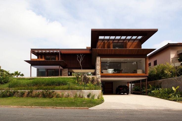 """A fachada oeste da casa M.A.N. aproveita a cota de nível mais alto do terreno para a entrada de garagem (inferior, rua) e a piscina (térreo). O terreno de esquina tem 180° de fachada, onde as coberturas em vidro para as varandas dos dormitórios e o spa (piso superior) e o fechamento, também de vidro, do living sobre a garagem captam massivamente a luz natural. A arquitetura, em """"T"""", é assinada por Gálvez"""