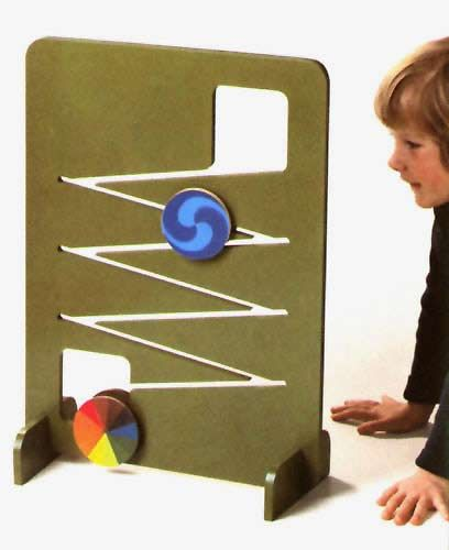 """Rollbahn (""""roller-run"""") color and movement toy, designed by Mike Ayres and Roger Limbrick, Switzerland, 1984, by Naef Spiele. The colored discs, with various designs and patterns, take almost a minute and a half to completely descend the zig-zag pattern of the frame, slowly mesmerizing with alternating shapes and visual trickery."""