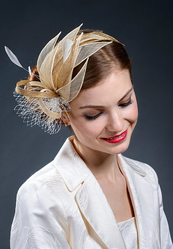 Beige and gold fascinator trimmed with ivory feathers and veil. Beautiful and elegant fascinator on a teadrop fascinator base trimmed with hand-rolled beige and gold leaves and loops. Finished with light ivory veil and delicate coques feathers. Fits to any headsize. Attached to the head with very thin (3mm wide) golden headband and small comb under the fascinators base. This way it stays very safely on your head and does not move away even if you decide to ride a horse at the races yourself…
