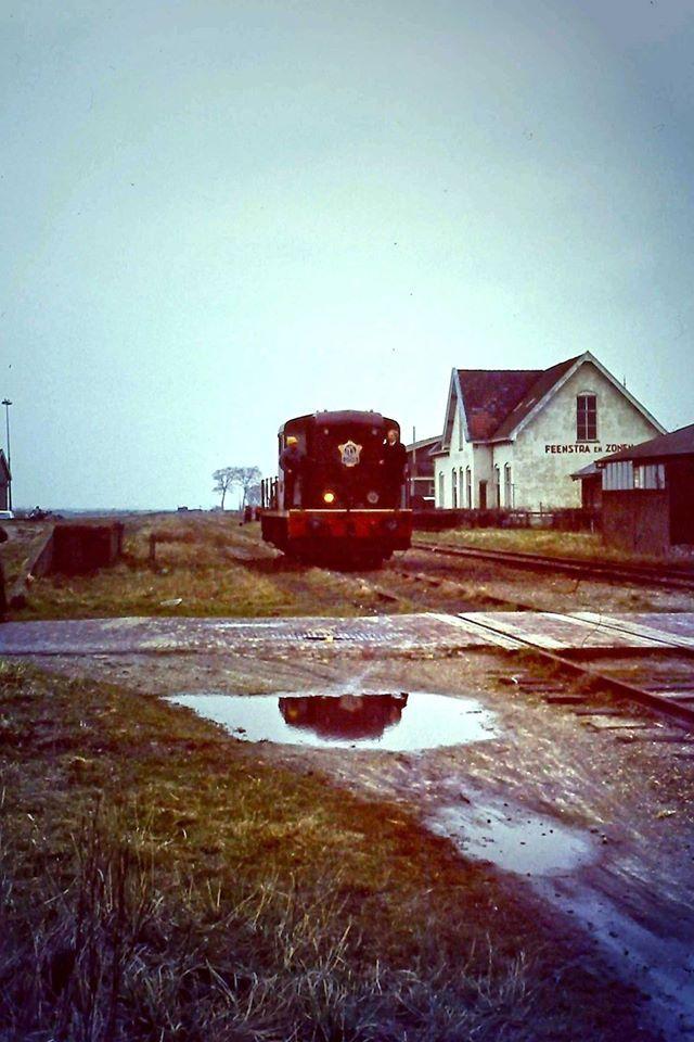 Spoorbaan met spoorwegovergang Aalsumerweg in 1972. De bomen in de verte staan aan de Mestslawiersterweg. Een beetje trieste foto eigenlijk. Ik heb er kunstmatig nog wat licht op laten schijnen, maar het loopt daar duidelijk naar zijn end....... zelfs die ene koplamp van de loc laat het afweten Jammer jammer jammer.