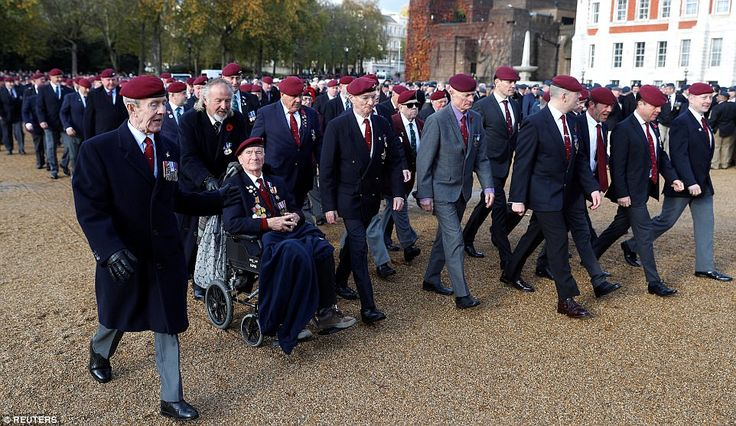 Veterans cross decked out in berets with war medals affixed to their chest make their way to the Cenotaph