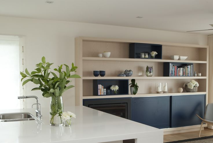 Open plan living dining kitchen with fireplace set within bookshelf joinery. Brooke Aitken Design