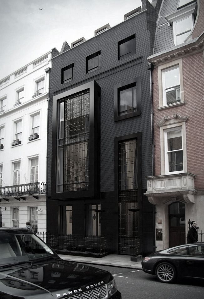 Featuring a slim and chic design, this London house was perfectly integrated in between the two existing buildings. The black facade makes it stand out as an individual structure.