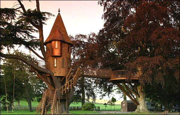 A dignified by whimsical 45-foot spire with cedar shingles, a copper turret, a side deck and two staircases with multilevel verandas adorn this lightening struck tree.  Scotland, by the TreeHouse Co.