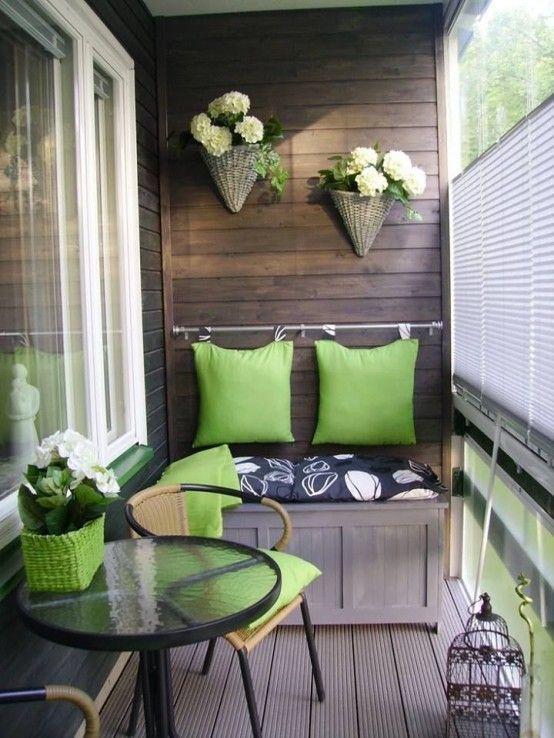 Coussins vert sur petit balcon avec fleurs au mur dans des paniers